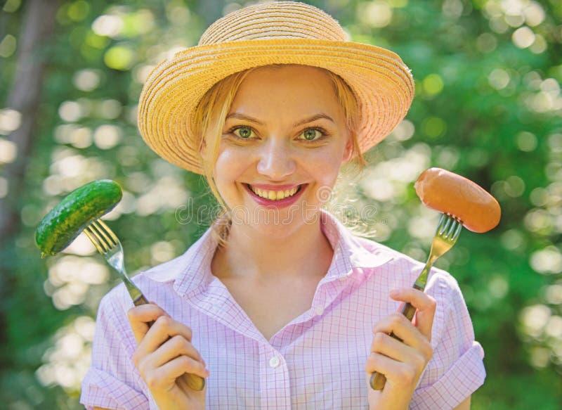 Wybór między mięsem lub warzywami Dziewczyny uśmiechnięta twarz trzyma rozwidlenia z kiełbasą i ogórkiem Alternatywny odżywianie  obrazy stock
