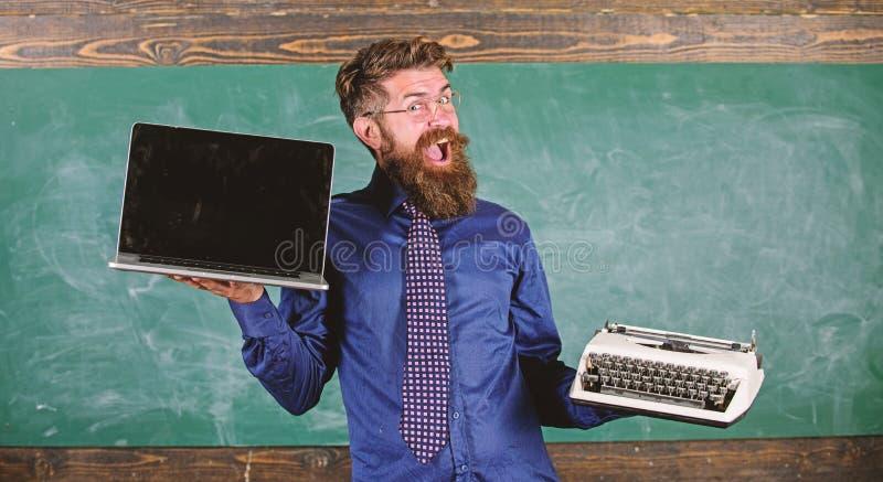 Wybiera prawą nauczanie metodę Nowożytny zamiast przestarzały Nauczyciela brodaty modniś trzyma maszyna do pisania i laptop naucz zdjęcia royalty free
