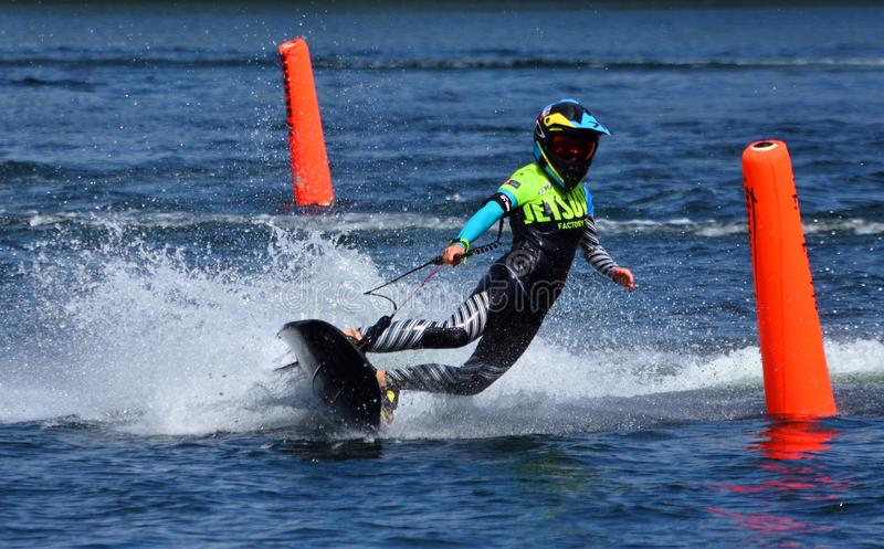 Female Motorsurf Competitor cornering at speed making a lot of spray. stock photo
