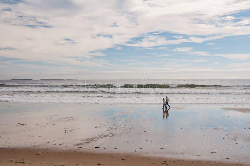 Wybrzeże Atlantycki ocean przy niskim przypływem i para starsi ludzi spaceruje wzdłuż piaska zdjęcie royalty free