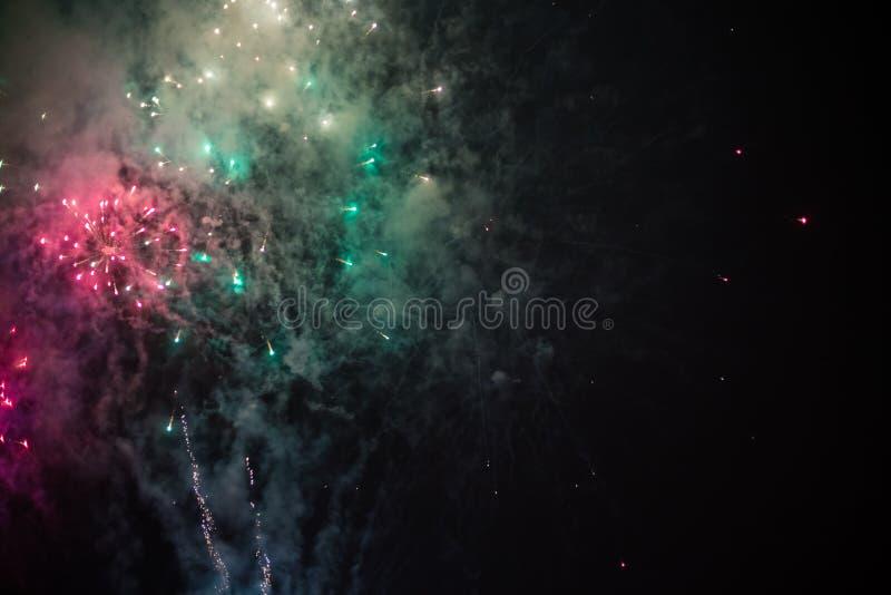 Wybuchowi i kolorowi wakacyjni fajerwerki przy nocnym niebem zdjęcie stock