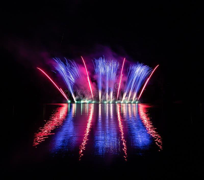 Wybuchy błękitny i czerwony ogień w bogatych fajerwerkach nad Brno tamą z jeziornym odbiciem zdjęcia royalty free