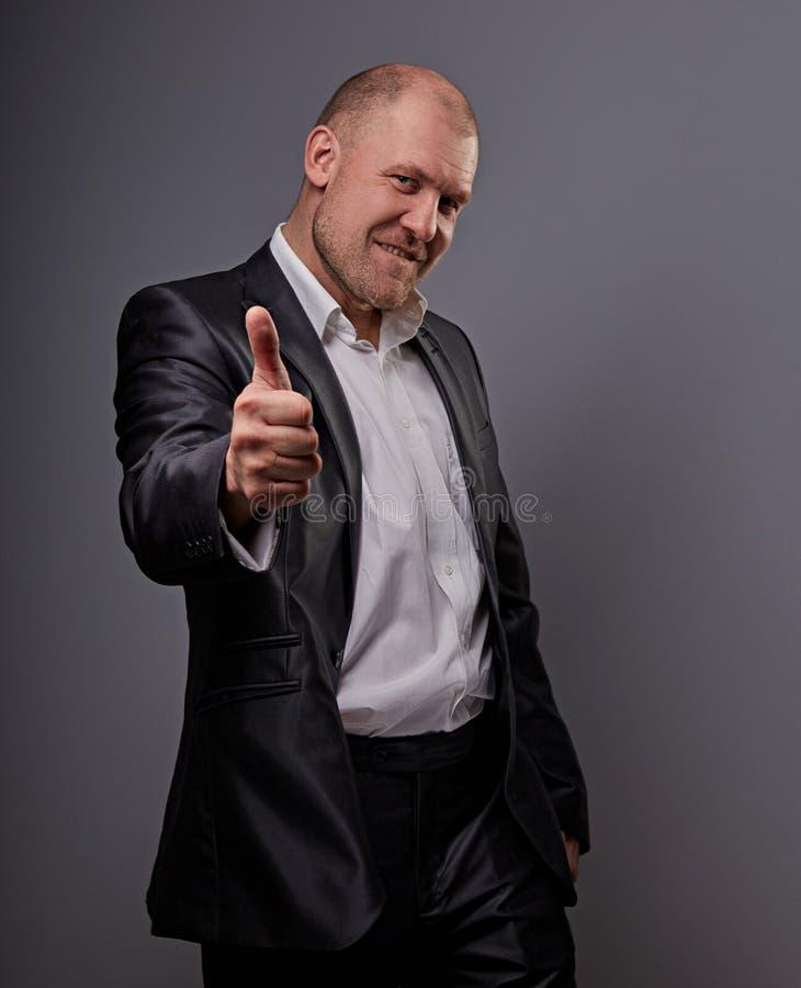 Wychodzący komiczny łysy biznesowy mężczyzna w czarnym kostiumu pokazuje palcowego sukcesu kciuk w górę znaka na popielatym tle z zdjęcie royalty free
