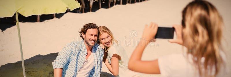 Wychowywa uśmiecha się podczas gdy córka fotografuje one przy plażą zdjęcia stock
