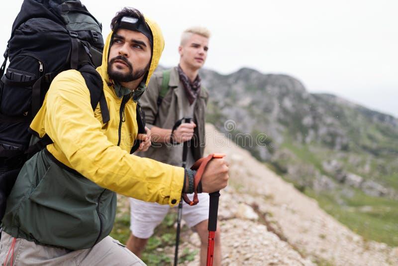 Wycieczkować z przyjaciółmi jest w ten sposób zabawą Grupa młodzi ludzie wycieczkuje wpólnie z plecakami obrazy stock
