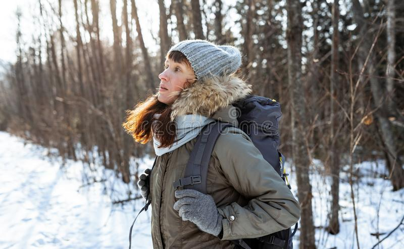 Wycieczkować: Dziewczyna w ciepłym kapeluszu z czerwonym włosy i wielkim plecakiem iść pieszo w zima lesie obraz royalty free