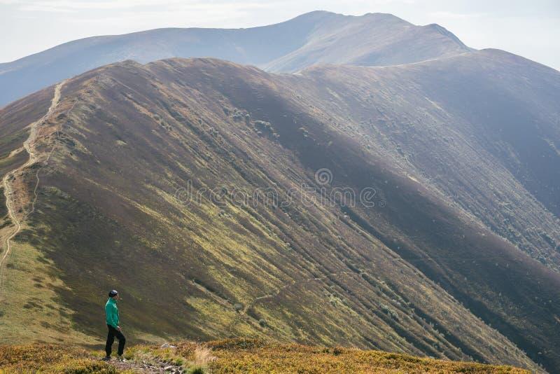Wycieczkować mężczyzna, arywisty lub śladu biegacza w górach, inspiracyjny krajobraz Niepłonny wycieczkowicz patrzeje widok górsk fotografia stock