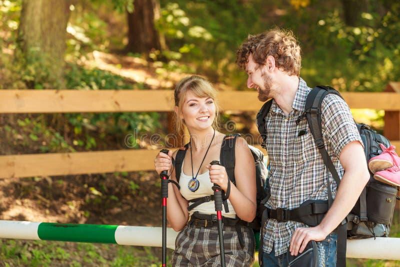 Wycieczkować par backpackers drałuje na lasowym śladzie fotografia stock