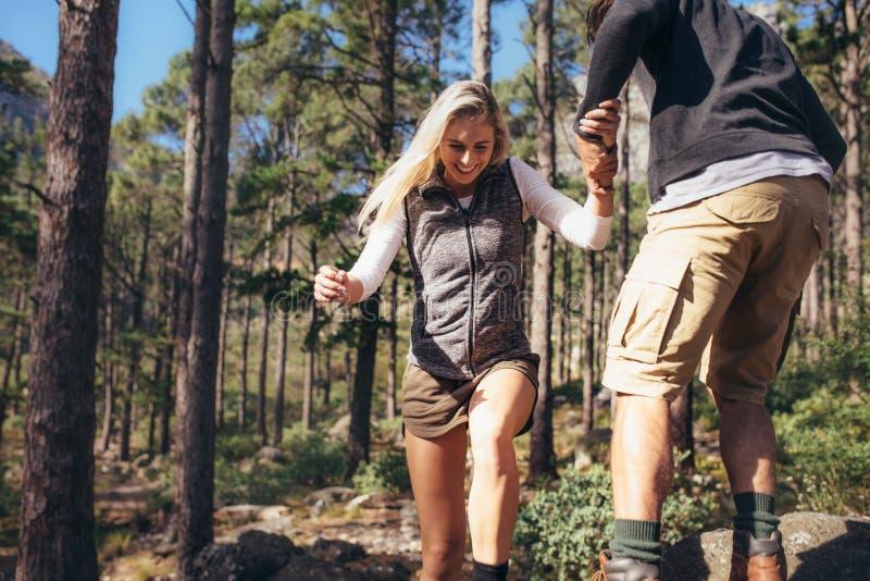 Wycieczkować pary odprowadzenie na skałach w lesie jest ubranym plecaki obrazy stock
