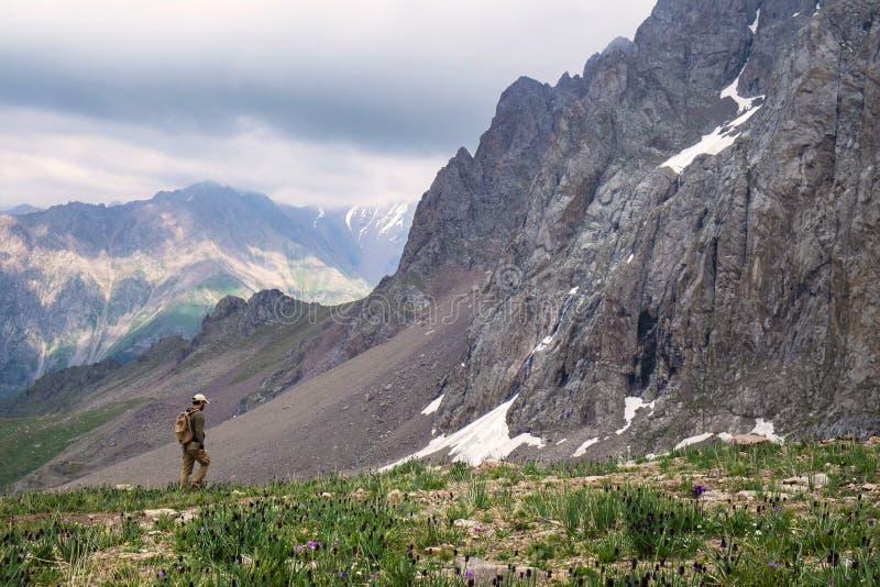 Wycieczkowicz dosięga dużą skałę w górach Kazachstan, Almaty obrazy stock