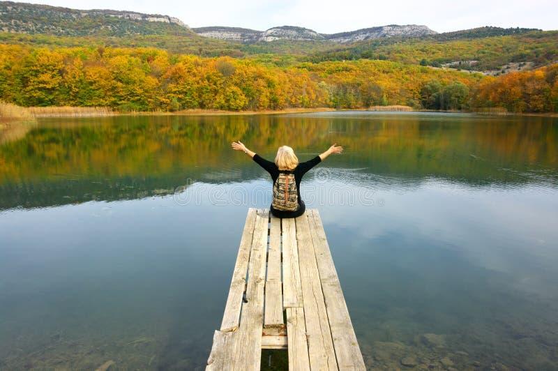Wycieczkowicz kobieta siedzi nad jeziorem w jesiennym dniu zdjęcie royalty free