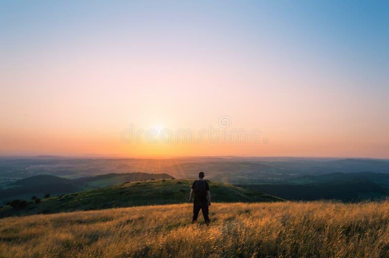 Wycieczkowicz na wzgórzu przyglądającym za Angielskim krajobrazie w kierunku położenia słońca na lato wieczór przez zdjęcia stock