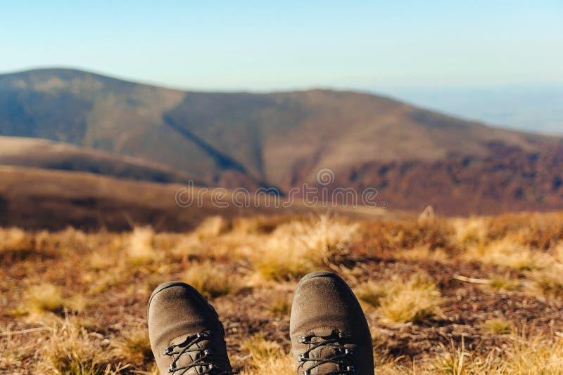 Wycieczkowicz relaksującego czas podczas plenerowy trekking w górach Wolno?ci i stylu ?ycia poj?cie Podróży tło, wycieczkuje buty obrazy stock