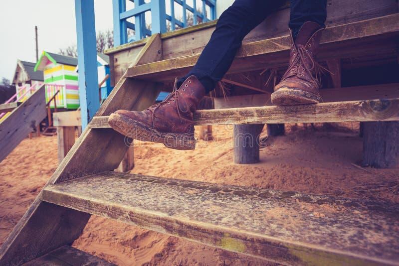 Wycieczkowicz relaksuje na krokach plażowa buda zdjęcie stock