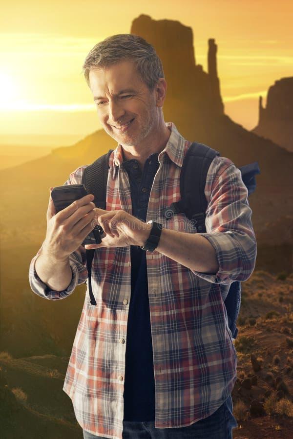 Wycieczkowicz Robi rozmowie telefoniczej w pustyni z telefonem kom?rkowym zdjęcia stock