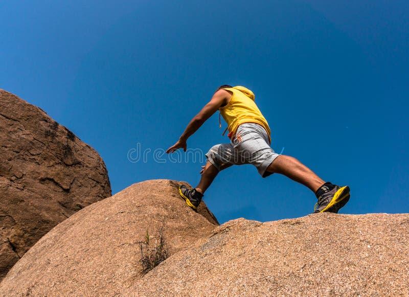 Wycieczkowicz skacze nad skałą obrazy stock