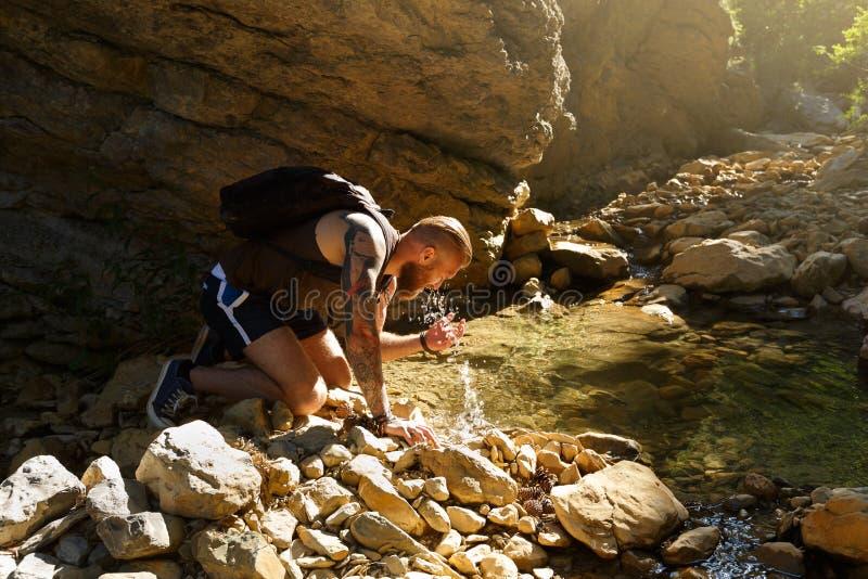 Wycieczkowicz woda pitna od rzeki Mężczyzna cieszy się czystą świeżą unpolluted wodę w halnej zatoczce zdjęcia stock