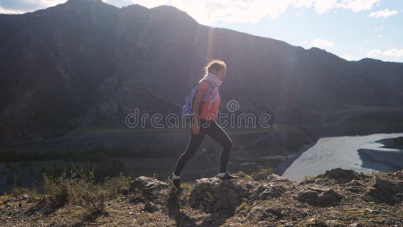 Wycieczkowicz wycieczkuje na górze góry z słońcem z plecakiem migocze Młoda Kobieta Zdrowy Aktywny styl życia Przygoda wewnątrz zdjęcie stock