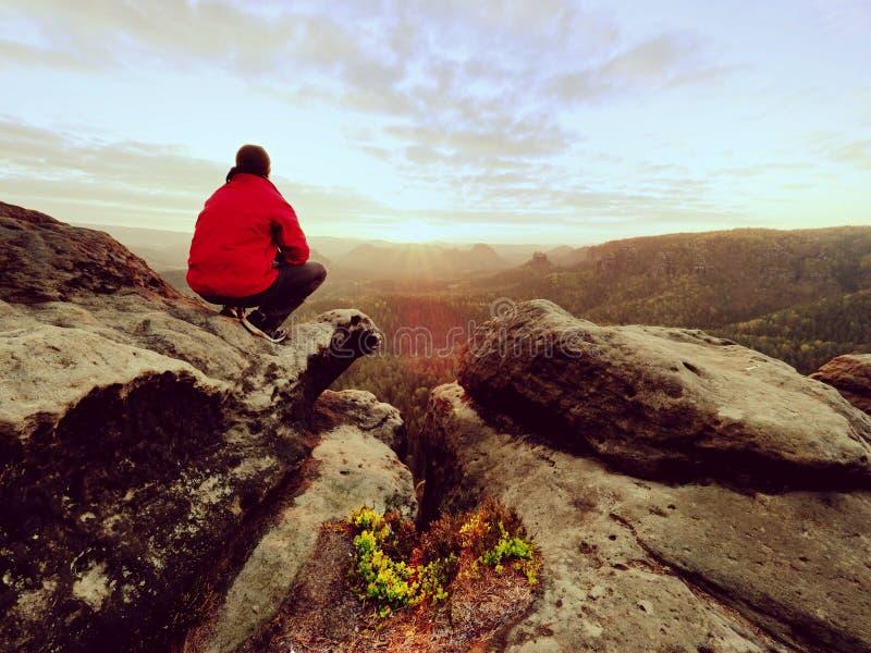 Wycieczkowicza mężczyzna bierze odpoczynek na halnym szczycie Mężczyzna kłaść na szczycie, bellow jesieni dolina zdjęcia royalty free