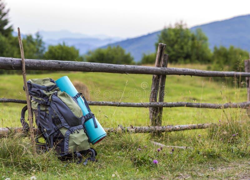 Wycieczkowicza obozuje plecak opiera na starym drewnianym ogrodzeniu Turystyczny equ zdjęcia royalty free