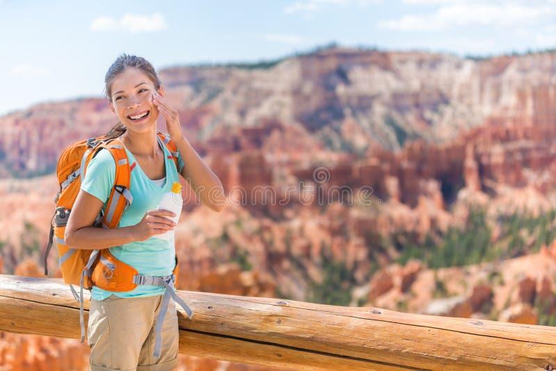 Wycieczkowicza sunscreen - kobieta wycieczkuje kładzenia sunblock obrazy royalty free