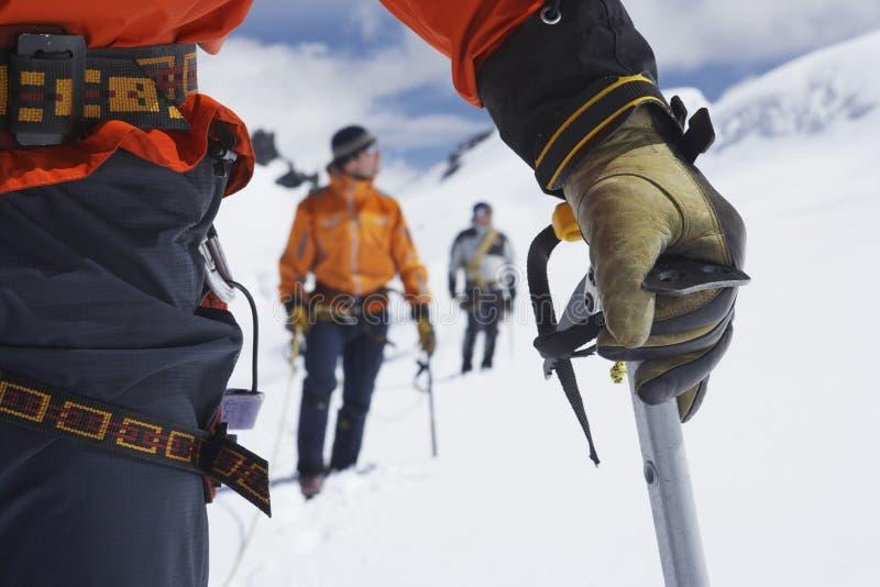Wycieczkowicze Używa Chodzących kije W Śnieżnych górach zdjęcia royalty free