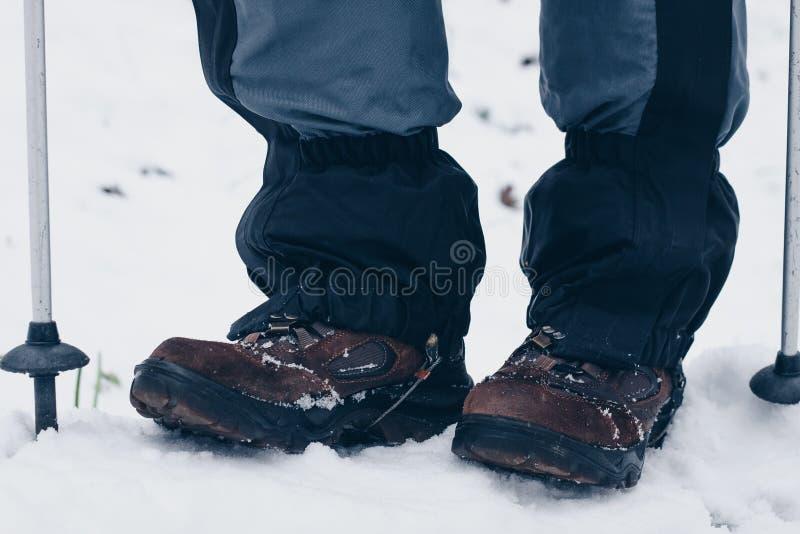 Wycieczkowiczy buty z trekking słupami i getry w zima lasu styl życia zdjęcia royalty free