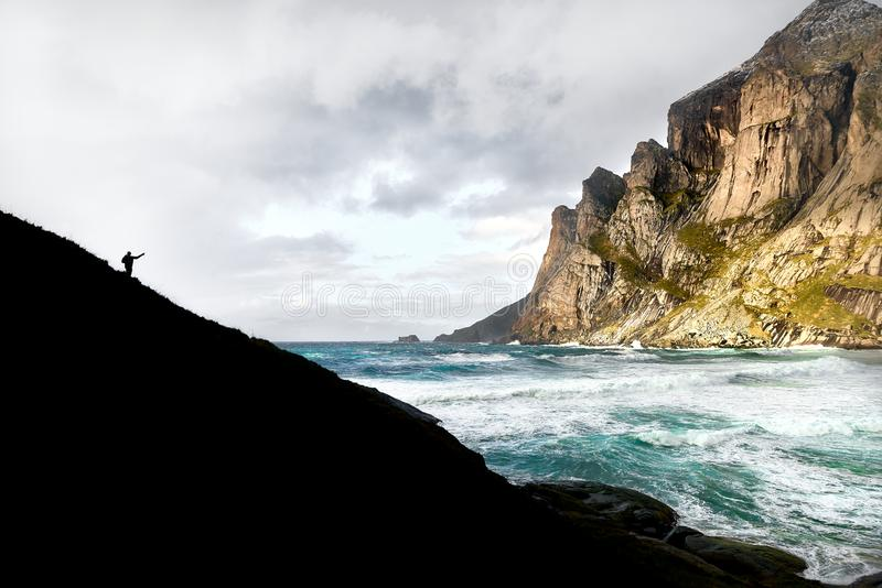 Wycieczkujący mężczyzna pozycję na falezie i wskazujący w kierunku masywnej góry na innym brzeg ocean na Lofoten wyspach we obrazy stock