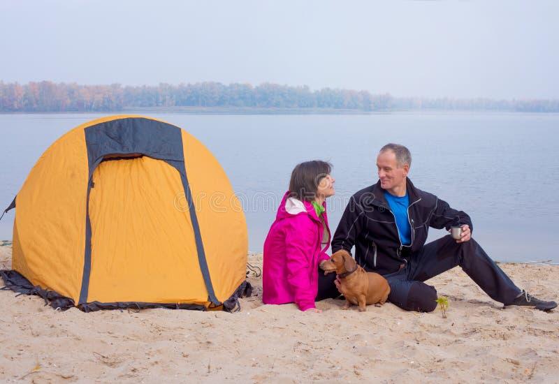 Wycieczkujący pary ma zabawę, bawić się z psem podczas gdy one relaxi obraz royalty free