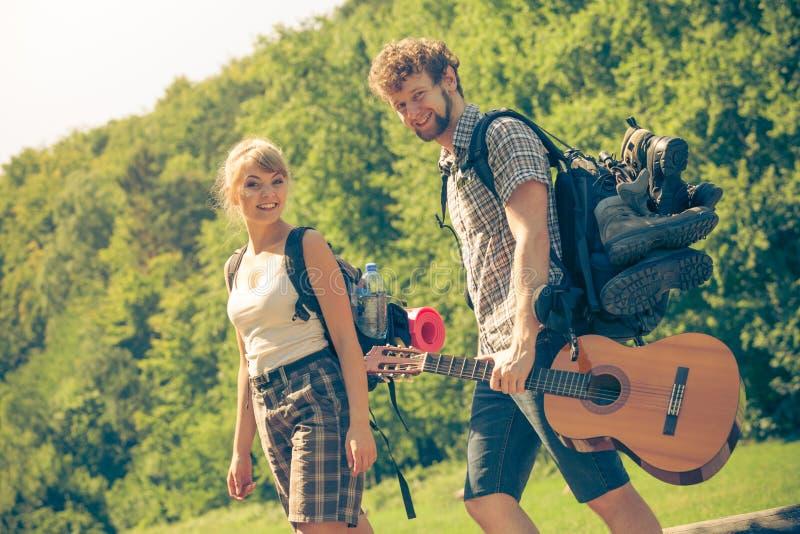 Wycieczkujący potomstwo pary z gitara plecakiem plenerowym fotografia stock