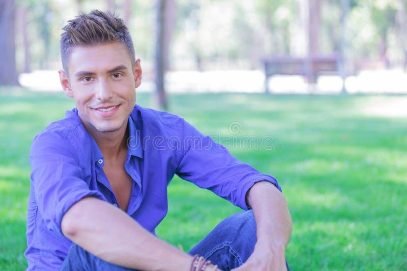 Model siedzi w trawie i ono uśmiecha się obraz stock