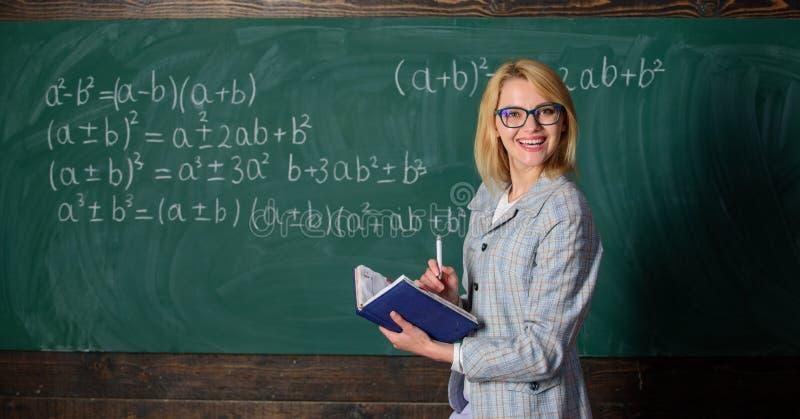 Wydajnego nauczania pogmatwanego nabywania istotna wiedza Kobieta uczy blisko chalkboard w sala lekcyjnej Ilości to zdjęcia royalty free