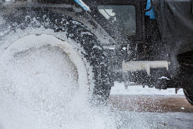 Wydmuszysko śniegu proszek od ciężarowego koła Zamazany koło i obniża fotografia royalty free