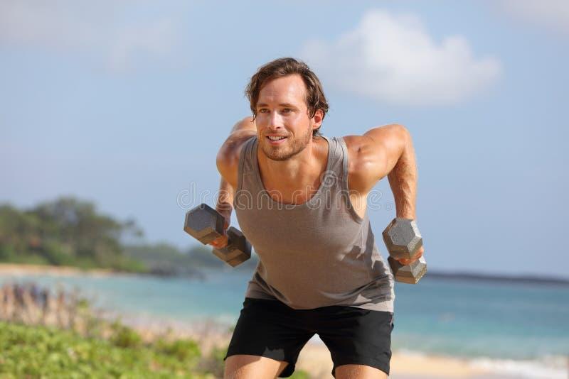 Wygięty na dwa kciuki — sprawny człowiek wykonujący ćwiczenia na stojąco w rzędzie z dwoma kajdankami AKA zdjęcia stock