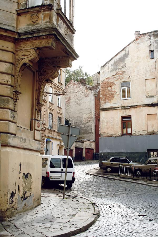 Wyginająca się ulica którego w górę iść, z drogą brukującą z brukowami, z samochodami i starymi domami zdjęcie stock