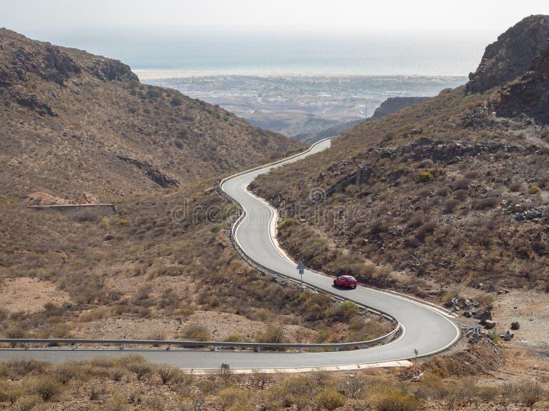 Wyginająca się wijąca droga z czerwonym samochodem w górach w Granie Canaria zdjęcie royalty free