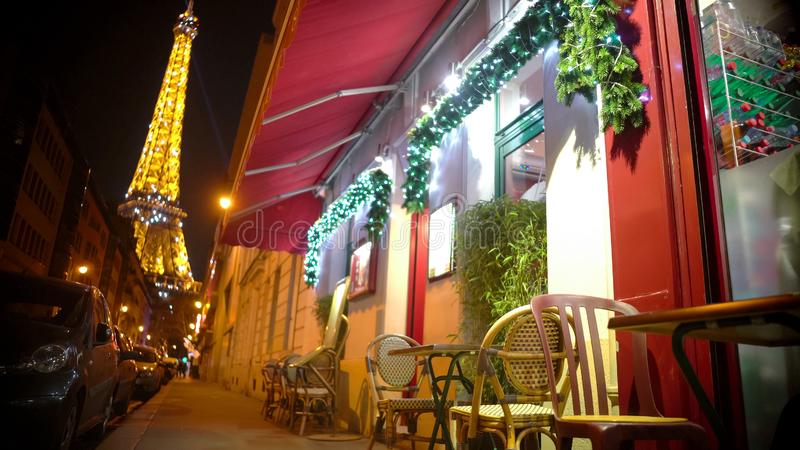 Wygodna Bożenarodzeniowa atmosfera w nocy Paryż, widok od ulicznej kawiarni przy wieżą eifla fotografia royalty free