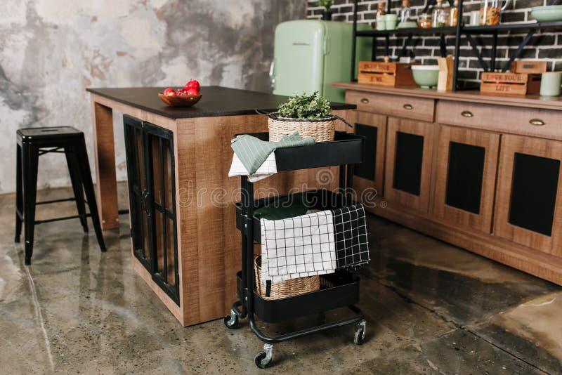Wygodna loft kuchnia z łomotanie stołem, krzesłami i metalu magazynem, dręczy na kołach - tramwaj zdjęcia stock