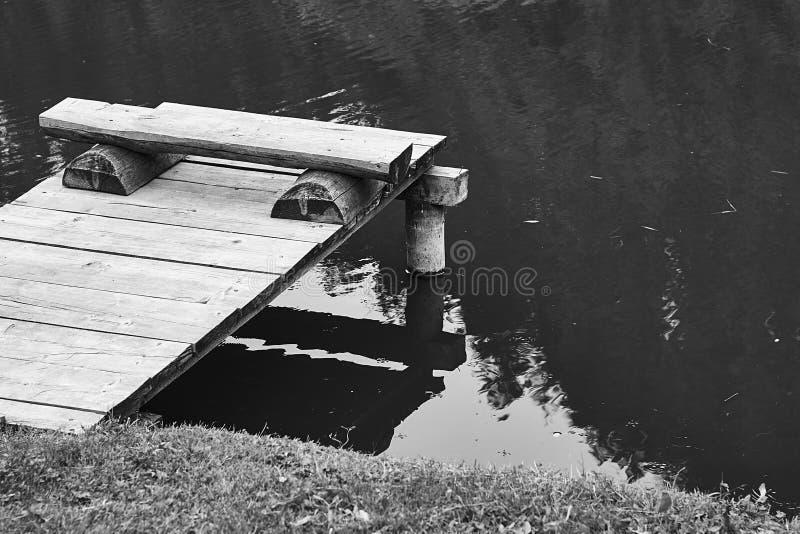 Wygodna połów ławka na drewnianym molu przy brzeg spokojny jezioro w lat nountains lub staw fotografia royalty free