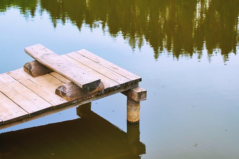 Wygodna połów ławka na drewnianym molu przy brzeg spokojny jezioro w lat nountains lub staw obraz royalty free