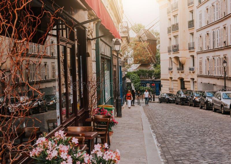 Wygodna ulica z stołami cukierniany i stary młyn w kwartalnym Montmartre w Pari fotografia royalty free