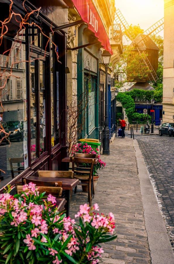 Wygodna ulica z stołami cukierniany i stary młyn w kwartalnym Montmartre w Paryż, obraz royalty free