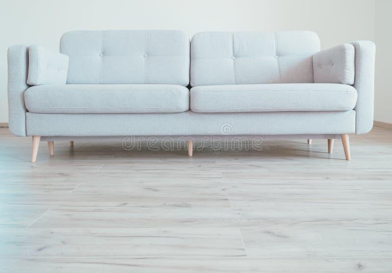 Wygodna współczesna scandinavian stylu kanapa na dębowej laminat podłoga obraz stock