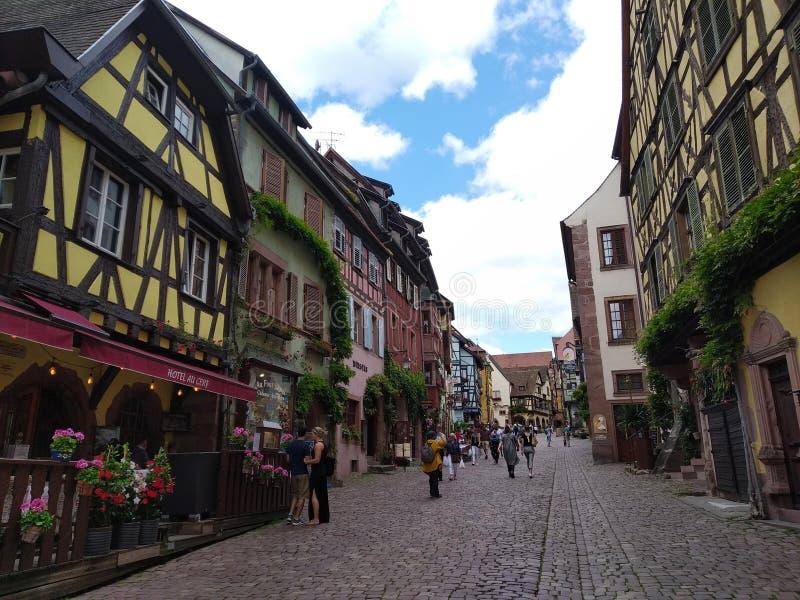 Wygodne restauracje dekorowali z kwiatami i domami z kolorowymi fasadami w ulicach Riquewihr zdjęcia royalty free