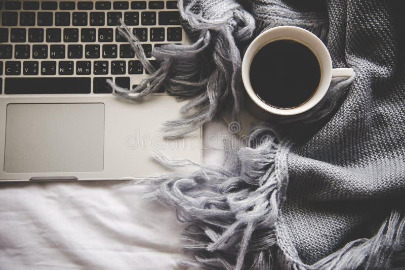 Wygodnej zimy domowy tło, filiżanka gorąca kawa z marshmallow, grże trykotowego pulower na białym łóżkowym tle, zdjęcia royalty free