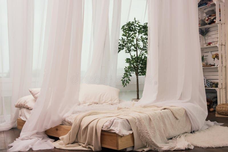 Wygodny łóżkowy pobliski okno z pięknymi zasłonami w pokoju zdjęcia royalty free