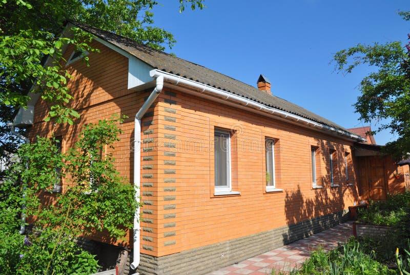 Wygodny cegła dom z starym azbesta dachem Podeszczowa rynna i ściana z cegieł fotografia royalty free
