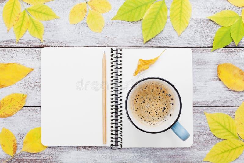 Wygodny jesieni śniadanie z ranek filiżanką kawy i otwartym notatnikiem na nieociosanym drewnianym stołowym odgórnym widoku Spadk fotografia stock