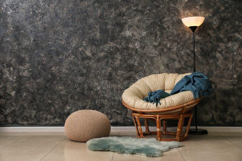 Wygodny karło z podłogową lampą i pouf blisko zmrok ściany w pokoju fotografia stock