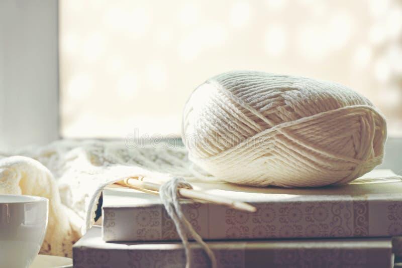 Wygodny zima dom z ciepłymi trykotowymi pulowerami i piłką przędza blisko windowsill, domowi hobby, obraz royalty free